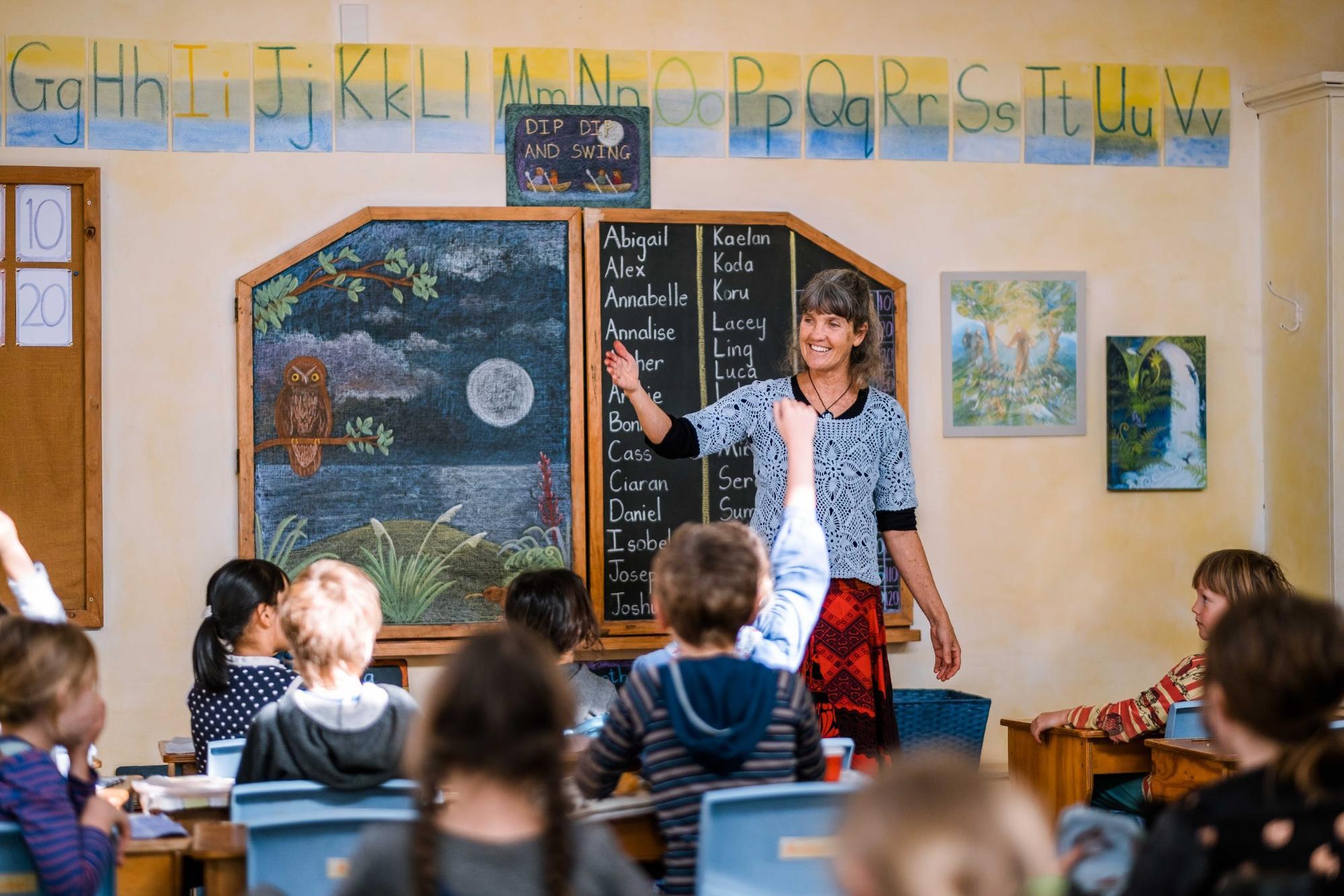 Teacher and children in Steiner school classroom